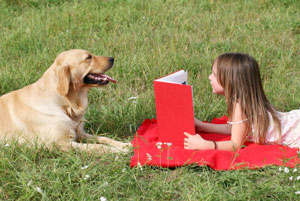Little girl reading to her dog.