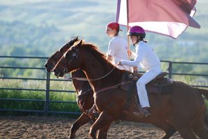 Madison Hawkinson and a teammate practicing formation riding with flags at a gallop